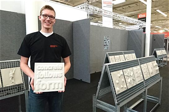 """Daniel Horn mit Sichtbeton-Kachel in der Ausstellung """"Bauen & Wohnen"""""""